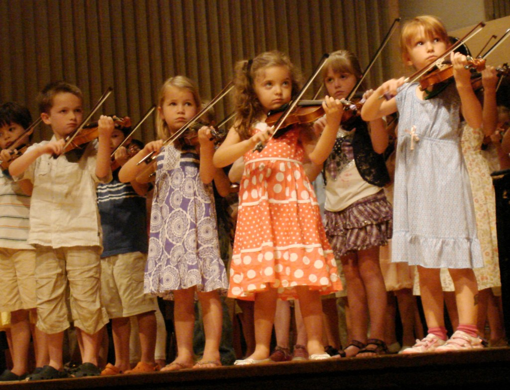 kids playing violin on stage